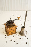 Manual coffee grinder and germal silver cezve (ibrik). On white background with scattered coffee grain royalty free stock image