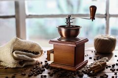 Manual coffee grinder on wooden table with window behind. Manual coffee grinder on wooden table royalty free stock photos