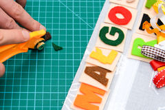 Manual cutting letters with colored sheets of felt Stock Images