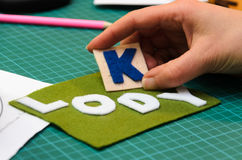 Manual cutting letters with colored sheets of felt Stock Image