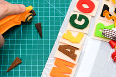 Manual cutting letters with colored sheets of felt Royalty Free Stock Image