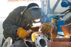 Manual electric arc welding of the junction Du 100 and flange royalty free stock image