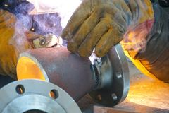 Manual electric arc welding of the junction Du 100 and flange royalty free stock photography