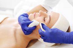Manual facial cleansing. The beautician cleans the woman`s skin. royalty free stock photo