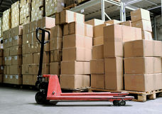 Manual fork pallet truck in warehouse. Group of carton boxes and fork pallet truck stacker in warehouse in front of cardboard boxes Stock Photos