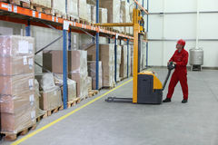 Manual forklift operator at work in warehouse. Worker in red uniform at work in warehouse stock image