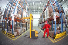 Warehousing - Manual forklift operator at work in. Worker in red uniform at work in warehouse - fish eye lens stock photo