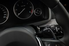 Manual gear changing stick on a car`s steering wheel. Modern car interior Royalty Free Stock Photo
