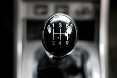 Manual gearbox in the car. Black shiny handle manual gearbox five-speed on the center of the frame royalty free stock images