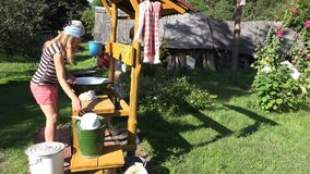 Manual hand laundry wash in bowl by poor peasant woman in farm house yard. 4K stock video footage