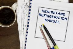 Manual for heating and refrigeration code concept. With coffee and book Royalty Free Stock Images