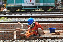 Manual laborer working masonry brick installing hand work. Construction, worker, building, work, industry, builder, helmet, working, safety, concrete, industrial royalty free stock photo