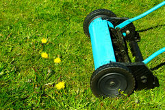 Manual lawn mower. A blue/green manual lawn mower on grass stock images