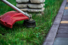Manual lawn mower on the background of green grass. Cut grass in not accessible places stock photo