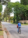 Manual mail deliveries by a postman on a bicycle in South Africa royalty free stock photo