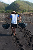 Traditional sea salt production on on the volcanic black sand, B. Manual male worker collects water for sea salt production in Amuk Bay, Bali, Indonesia. It is Royalty Free Stock Image