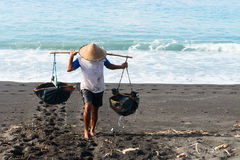 Traditional sea salt production on the volcanic black sand, Bali. Manual male worker collects water for sea salt production on volcanic black sand in Amuk Bay Stock Images