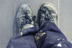 Manual man worker old shoes detail high view. Dirty pants royalty free stock photo