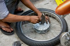 Manual motorbike wheel repair on street. Street manual motorbike wheel repair in Vietnam Royalty Free Stock Images