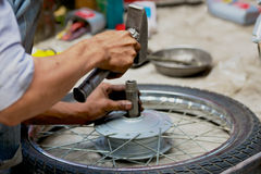 Manual motorbike wheel repair on street Royalty Free Stock Images