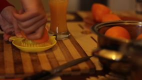Manual Orange Squeeze. An orange is squeezed by hadn for preparing a natural healthy orange juice stock footage