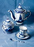 Manual painting of dishes. White and dark-blue  tea set on the blue drapes Stock Image