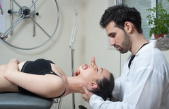 Manual, physio and kinesio therapy techniques performed. By a male physiotherapist on a training plastic spine and a female patient stock photo