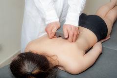 Manual, physio and kinesio therapy techniques performed. By a male physiotherapist on a training plastic spine and a female patient Stock Photography