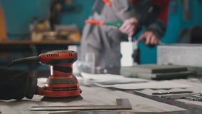 Manual sander sanding a metal detail at the factory, de-focused. Industrial concept royalty free stock photos