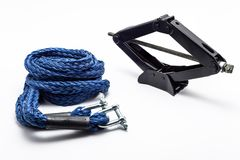 Manual scissor car jack and car tow rope, isolated on a white background with a clipping path. Manual scissor car jack and car tow rope, isolated on a white stock photo