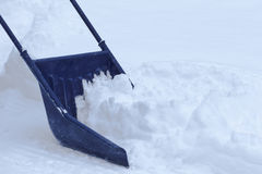 Manual snow removal with snow scoop after blizzard. Manual snow removal from driveway using a snow scoop after blizzard stock photo