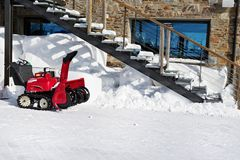 The manual snowplow in the yard of the house. The red petrol snow blower in sunny winter day at a snowdrift under a street ladder stock photo