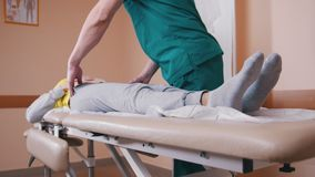 Manual therapist massaging and examining a young woman lying on a massage table stock footage