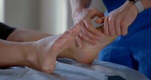 Manual therapist is massaging feet of female patient in osteopathic clinic, curing of diseases
