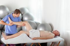 Manual therapy - young physiotherapist bending male patient knee during massage. Manual therapy - young physiotherapist bending caucasian male patient knee royalty free stock photo