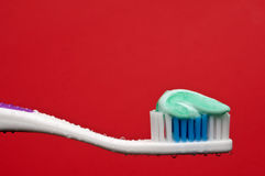 A manual toothbrush with toothpaste on red Royalty Free Stock Photo