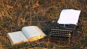 Manual Typewriter And Opened Book On The Grass At stock video