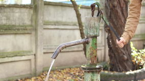 Manual Water Pump. Person using a mechanical pump for suction fresh water. Hand pumps are manually operated pumps; they use human power and mechanical advantage stock footage