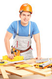 Manual woker standing next to a table with equipment and wooden Stock Image