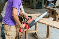 Manual wood concept. Profile side view cropped photo of cabinetmaker handyman tradesman holding chainsaw in hands sawing wood. Board make furniture in work shop stock photos