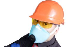 Manual worker. The builder in a building helmet and a gas mask on the isolated white background Stock Images