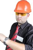 Manual worker. The young builder in a building helmet looks at time for the isolated white background Royalty Free Stock Photo