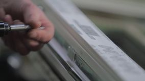 Manual worker assembling PVC doors and windows. Kyiv, Ukraine - June, 2017: The employee installs the accessories on the plastic window in the workshop of the stock footage