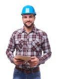 Manual worker in blue helmet with digital tablet Royalty Free Stock Image