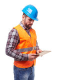Manual worker in blue helmet. And shirt using a digital tablet, isolated on white Royalty Free Stock Image