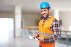 Manual worker in blue helmet using a digital tablet Stock Photos