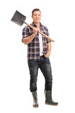 Manual worker in boots holding a shovel Stock Photography