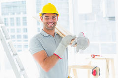 Manual worker carrying planks in building Stock Photography