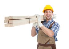 Manual worker carrying wooden planks. Full length portrait of young manual worker carrying wooden planks over white background royalty free stock photos
