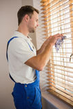 Manual worker cleaning blinds with a towel Stock Images